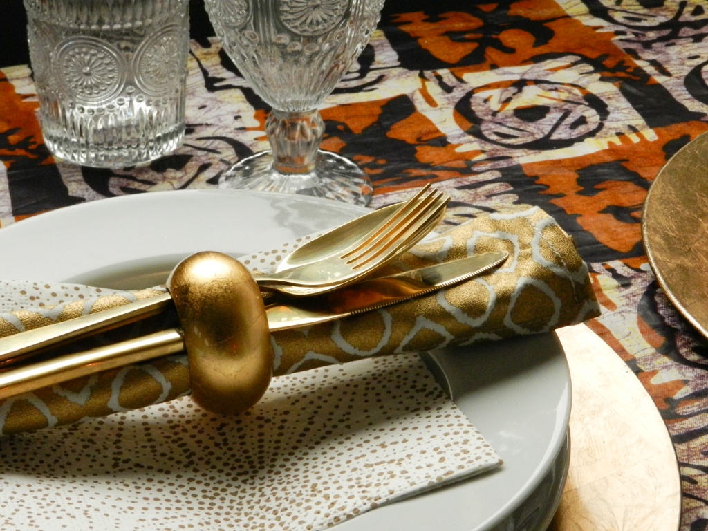 xmas table covered in brown and cream ankara fabric with gold and white accessories