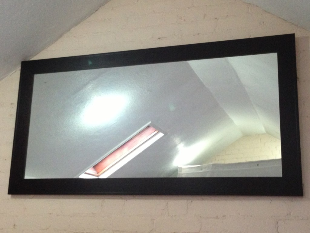 a rectangular wooden framed mirror