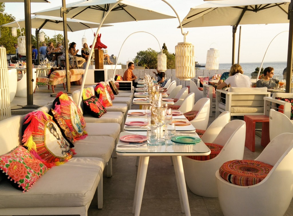 colourful restaurant rooftop seating area with colourful cushions and dinner plates