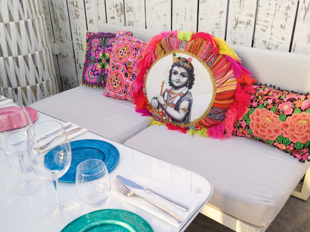 Brightly coloured cushions on a white bench with blue and green plates on a table