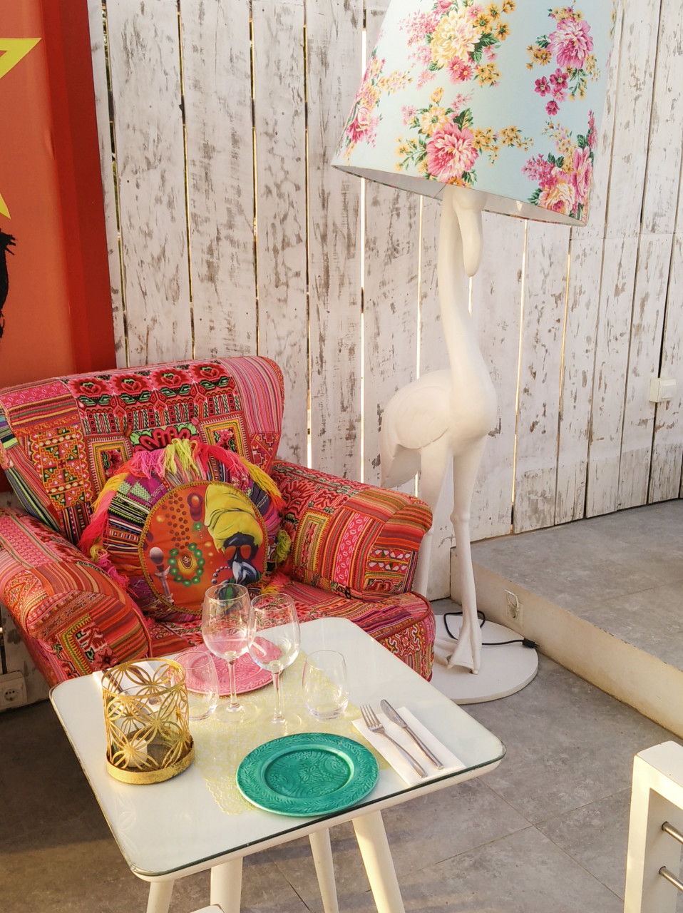 patchwork armchair next to a flamingo floor standing lamp with a floral shade