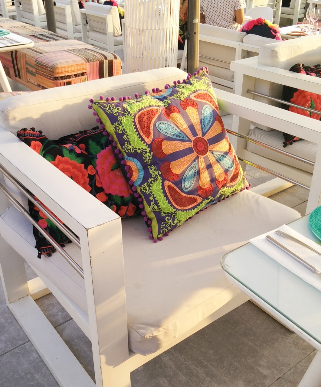 brightly coloured cushions on a white chair
